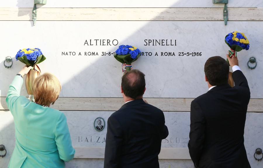 Italian Premier Matteo Renzi, right, German Chancellor Angela Merkel, left, and French President Francois Holland pay their homage at the tomb of Altiero Spinelli, one of the founding fathers of European unity, in the cemetery of the island of Ventotene, Italy, Monday, Aug. 22, 2016. Standing silently together, the three leaders placed three bouquets of blue and yellow flowers, the colors of the European Union, on the simple white marble tombstone of Altiero Spinelli in the cemetery of the island of Ventotene. (Carlo Hermann/Pool Photo via AP)